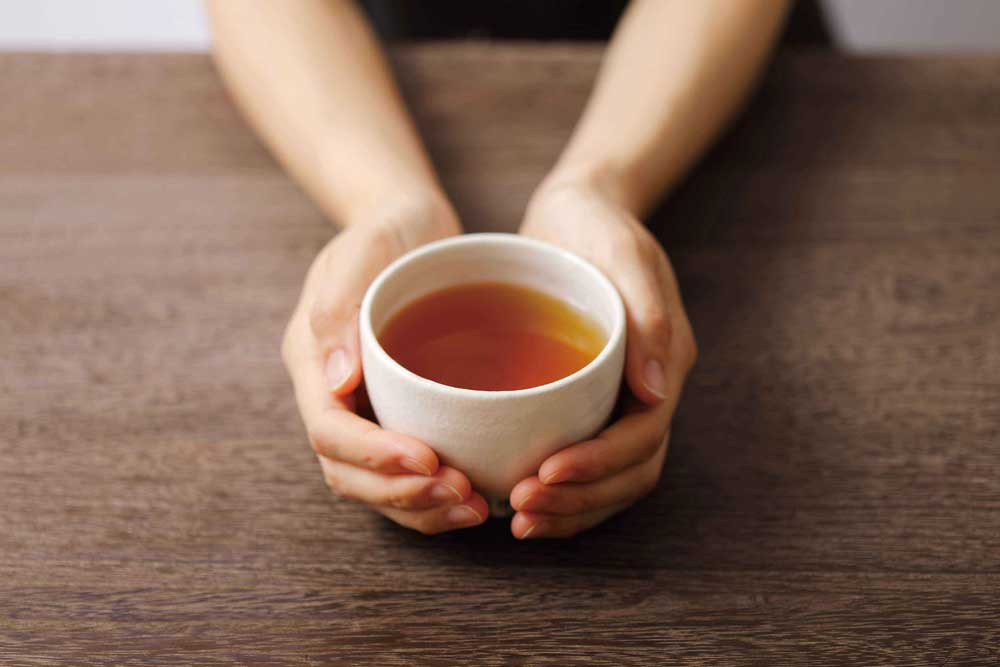 ほうじ茶が入った湯のみ持ってる人の写真